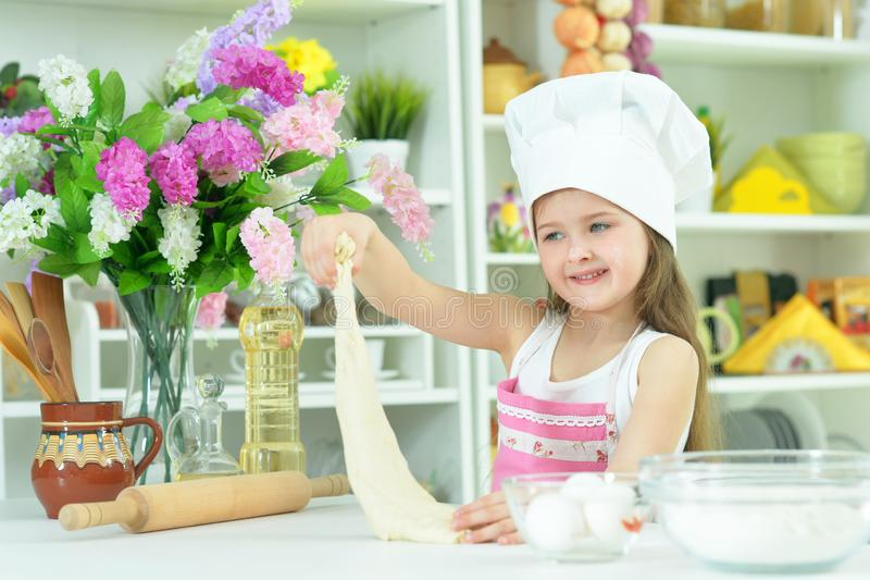 Portrait of young girl baking in the kitchen. Young beautiful girl baking and posing in the kitchen at home royalty free stock image