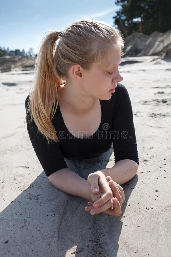 Portrait of young girl in black dress with long blonde hair lying on beach royalty free stock photos