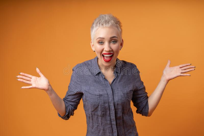 Portrait of young girl with blond short hairstyle looking at camera and laugh isolated on orange background with copy space royalty free stock images