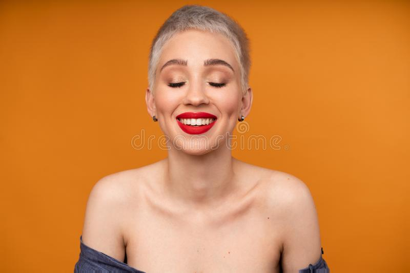 Portrait of young girl with blond short hairstyle looking at camera and laugh isolated on orange background with copy space. Woman surprised and smiling stock photography