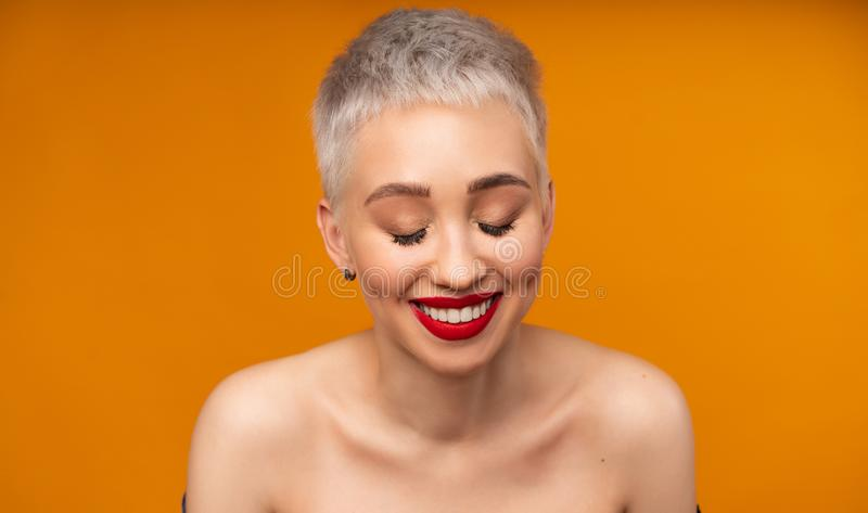 Portrait of young girl with blond short hairstyle looking at camera and laugh isolated on orange background with copy space. Woman surprised and smiling royalty free stock photo