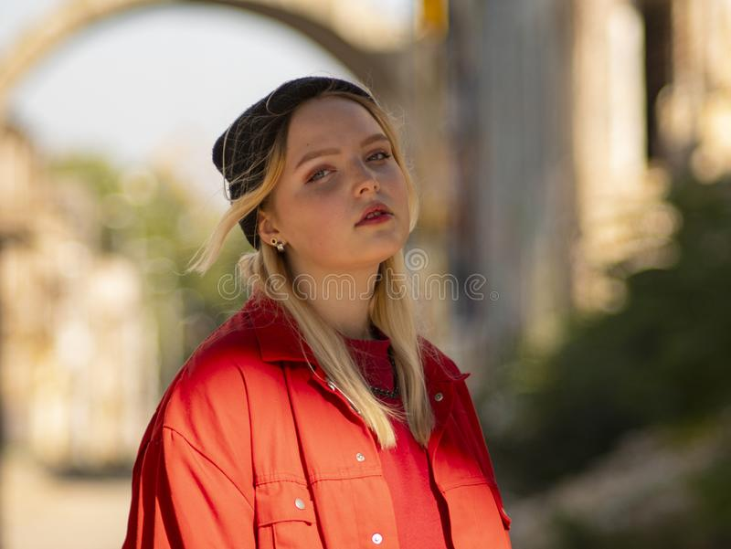 Portrait of a young girl blonde teenager in a knitted black hat on the street royalty free stock photos