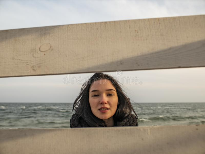 Portrait of a young girl with brown hairs view through a wooden fence on the background of the sea royalty free stock image