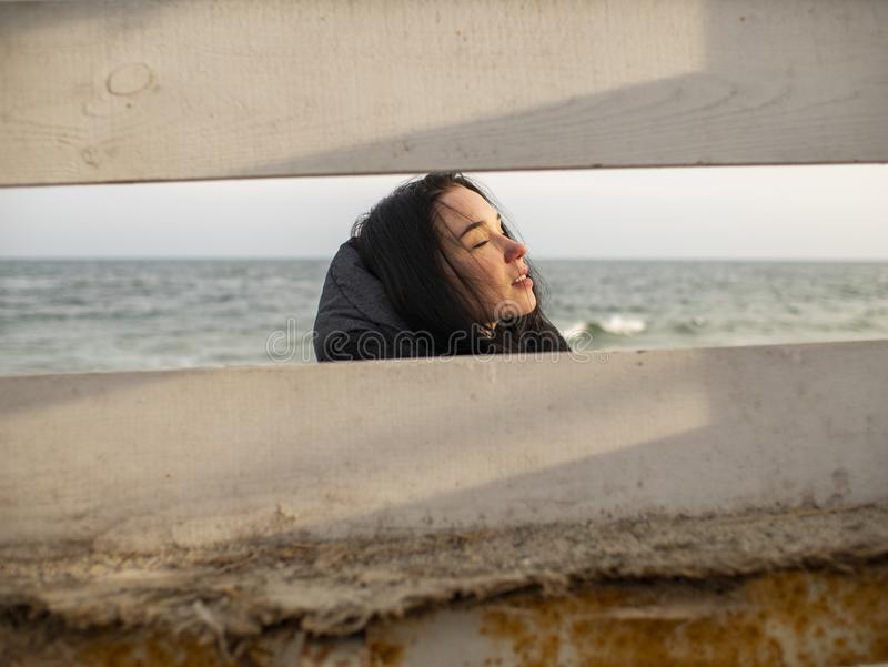 Portrait of a young girl with brown hairs view through a wooden fence on the background of the sea stock photo