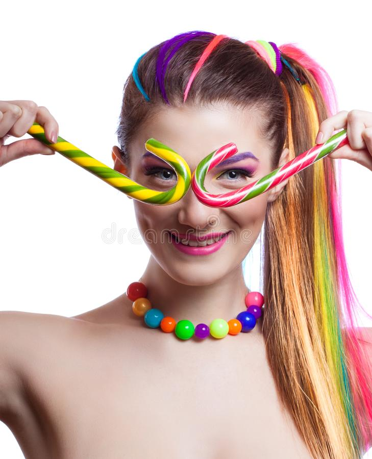 Portrait of a young girl with colorful creative makeup and colored strands of hair. The woman holds in hands colored candy. royalty free stock photos