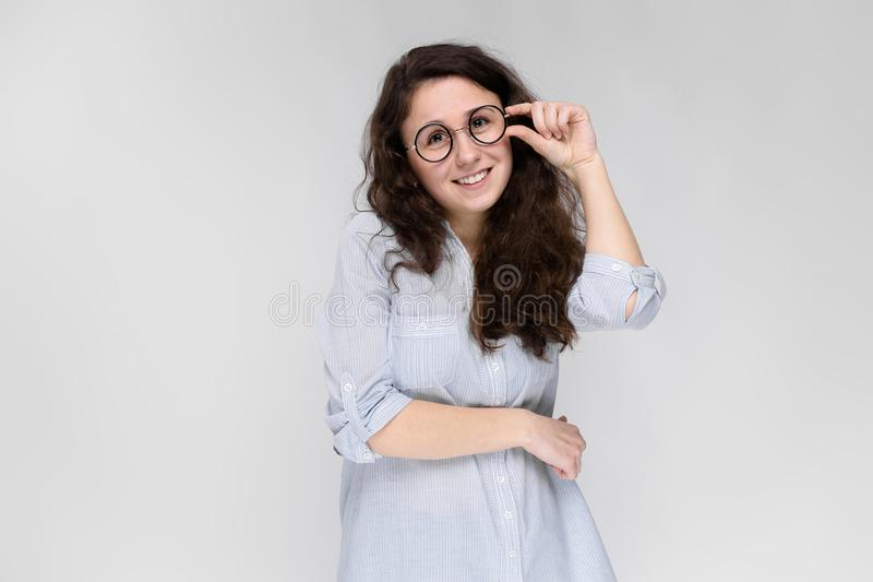 Portrait of a young girl in glasses. Beautiful young girl on a gray background. A young girl in a light blouse and dark stock photo