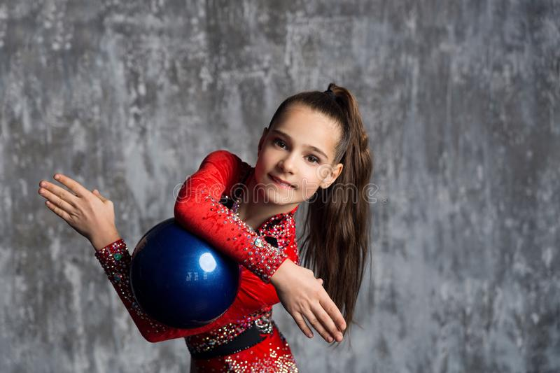 A portrait of young girl gymnast in a red suit makes exercise with a ball against a gray wall. She holds the ball between her hand. S and smiles royalty free stock photo