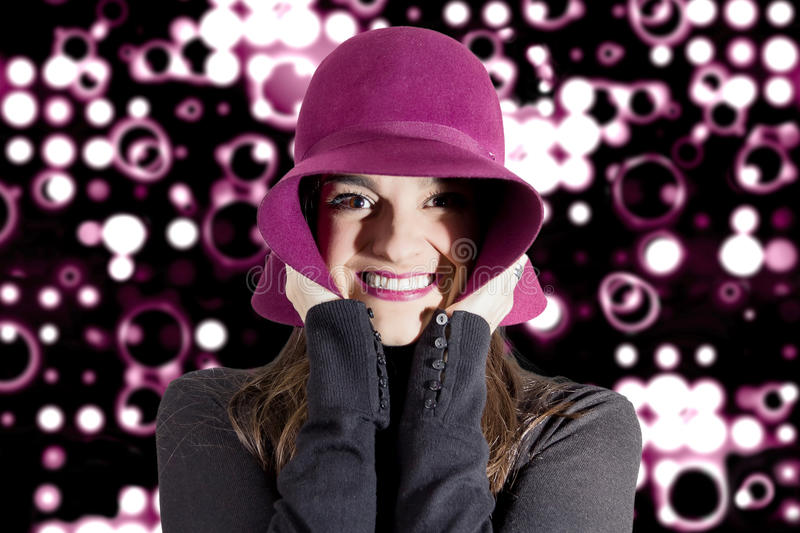 Portrait of young girl with a hat in front of spotlights background royalty free stock image