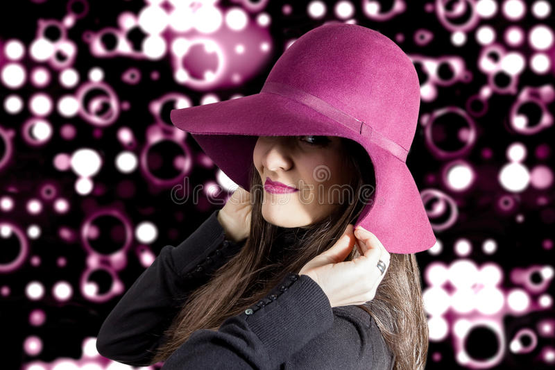 Portrait of young girl with a hat in front of spotlights background royalty free stock photos