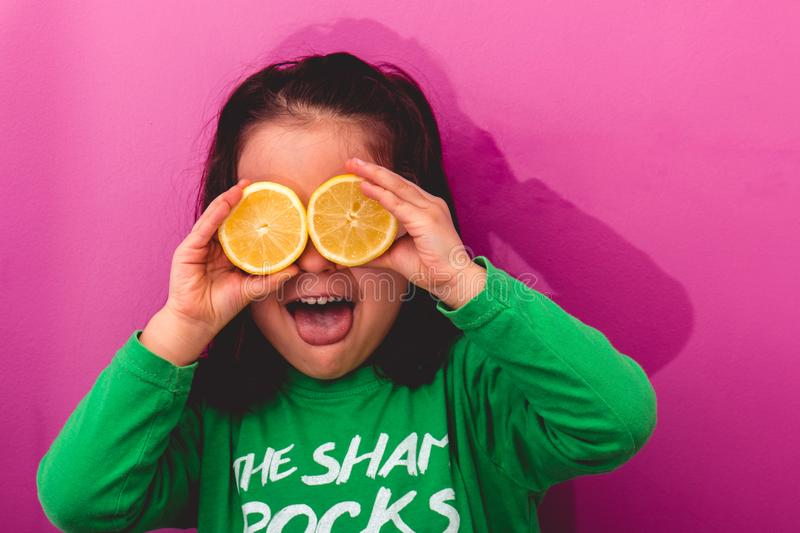 Portrait of a young girl holding two sliced lemons in her eyes stock photography