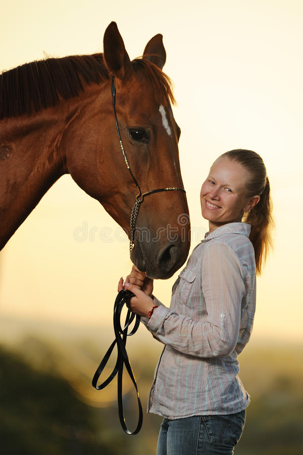 Portrait of young girl with horse at the sunset stock images