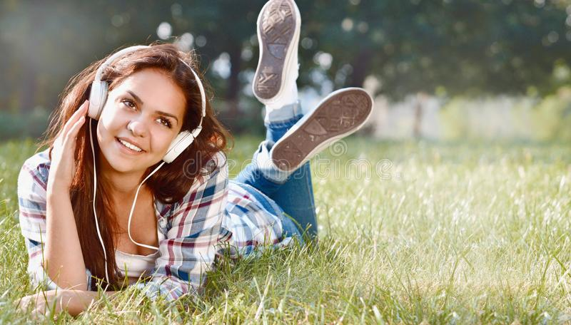Portrait of young girl listening music lying at the grass stock photo