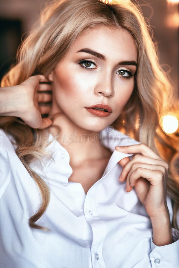 Portrait of a young girl looking into the camera. Model posing in a white shirt stock photo