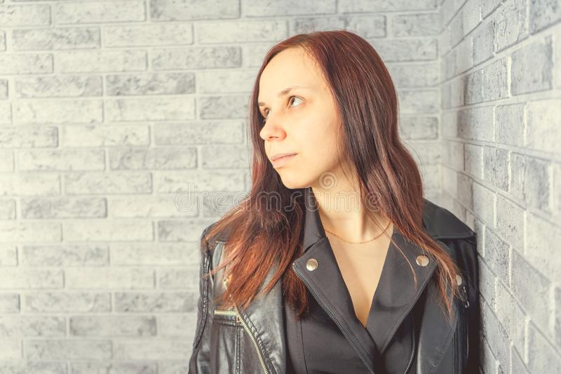 Portrait of a young girl without makeup on her face in a black jacket against a gray brick wall. royalty free stock photo