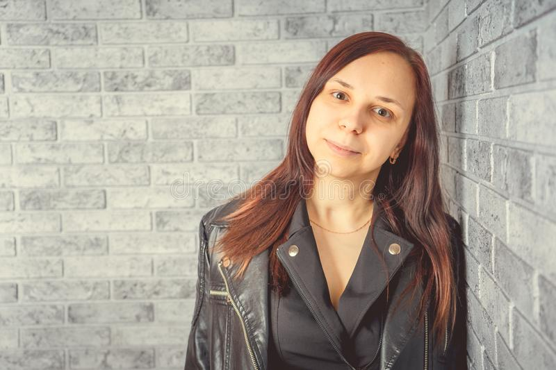 Portrait of a young girl without makeup on her face in a black jacket against a gray brick wall. stock photos