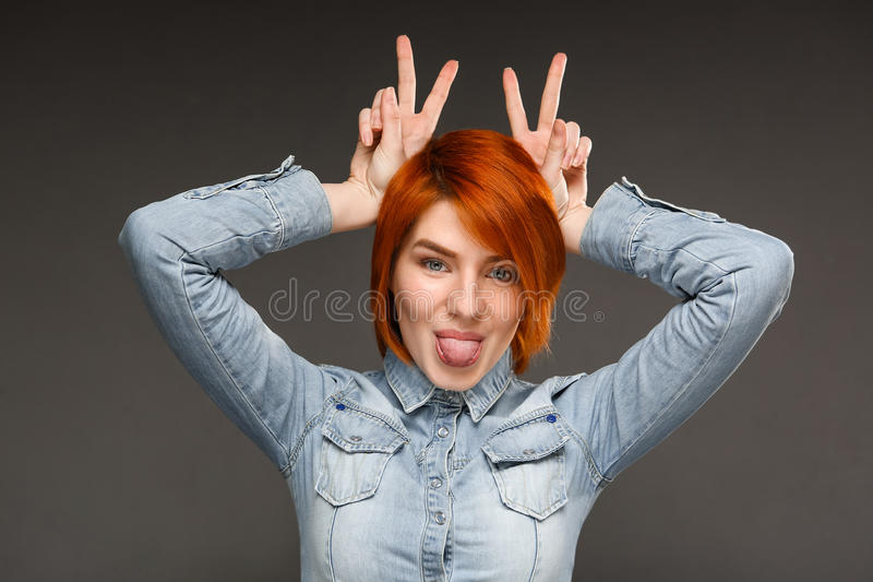 Portrait of young girl over grey background. Portrait of young confident girl with red hair smiling, showing tongue, looking at camera over grey background royalty free stock image