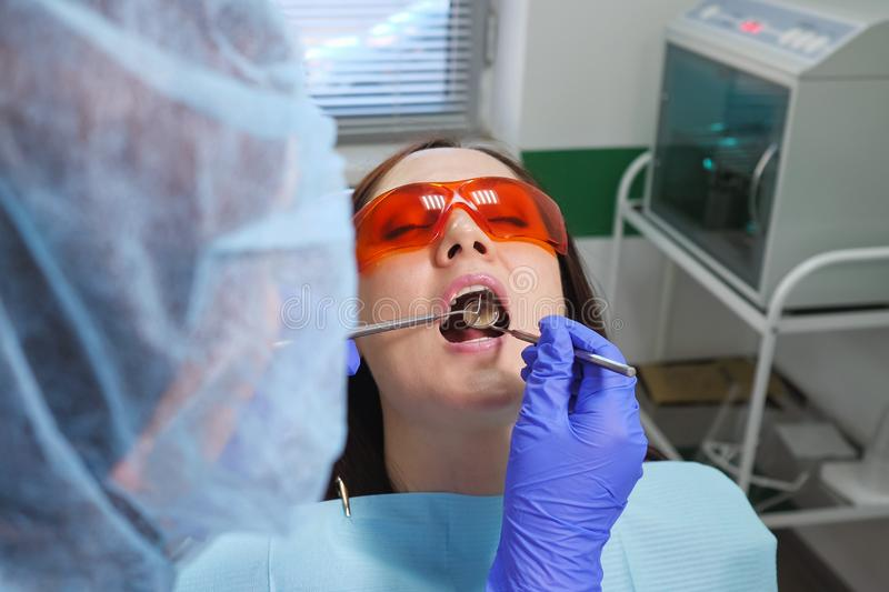 Young girl in protective glasses on preventive examination in dental chair at the dentist clinic. Teeth care concept. Portrait of young girl in protective stock image