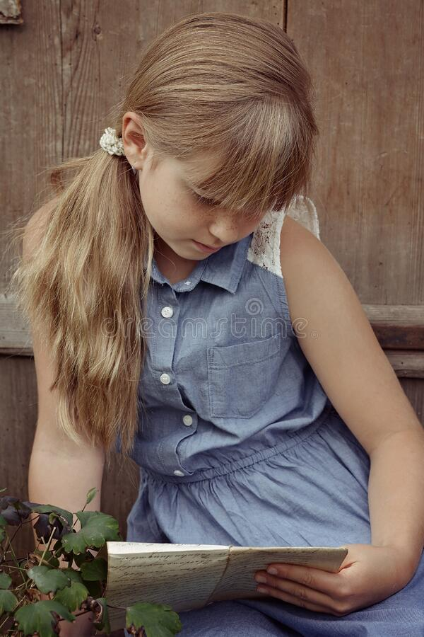 Portrait of young girl reading outdoors royalty free stock images