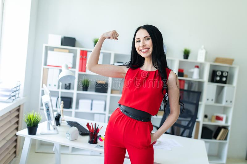 Beautiful young girl in a red suit stands in the office and shows a muscle on her arm. royalty free stock photo