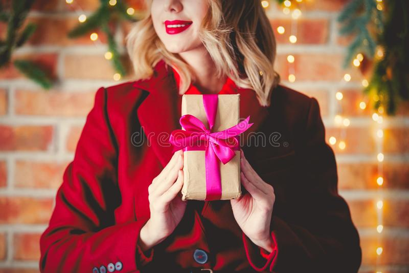Girl in red coat with gift box stock photography