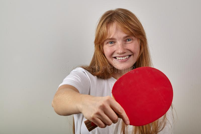 Portrait of young girl with red hair and freckles dressed in white t-shirt holding table tennis racket stock images
