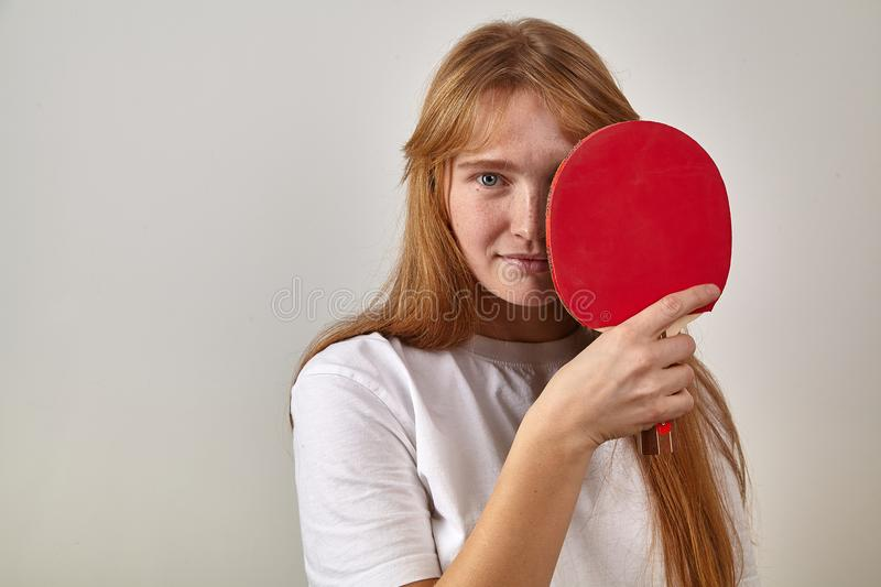 Portrait of young girl with red hair and freckles dressed in white t-shirt holding table tennis racket royalty free stock photos