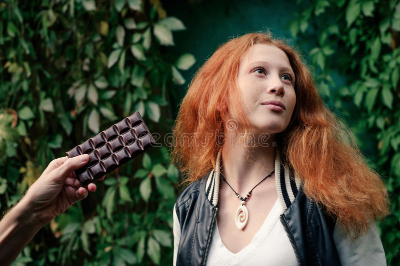 Portrait of young girl with red hair, refuse from chocolate bar royalty free stock photo
