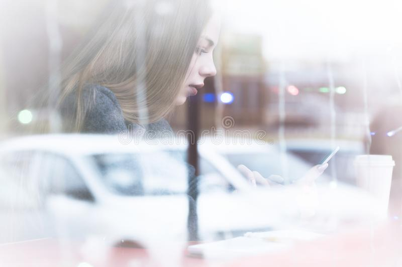 Portrait of a young girl sitting in a cafe outside the window with a reflection of the street looking into the phone stock image