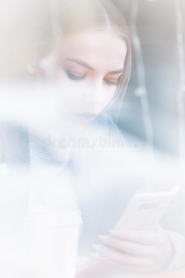 Portrait of a young girl sitting in a cafe outside the window with a reflection of the street looking into the phone stock images