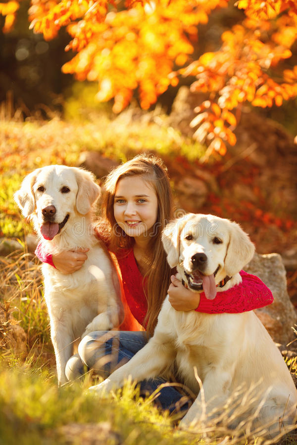 Portrait of Young girl sitting on the ground with her dog retriever in autumn scene royalty free stock photo