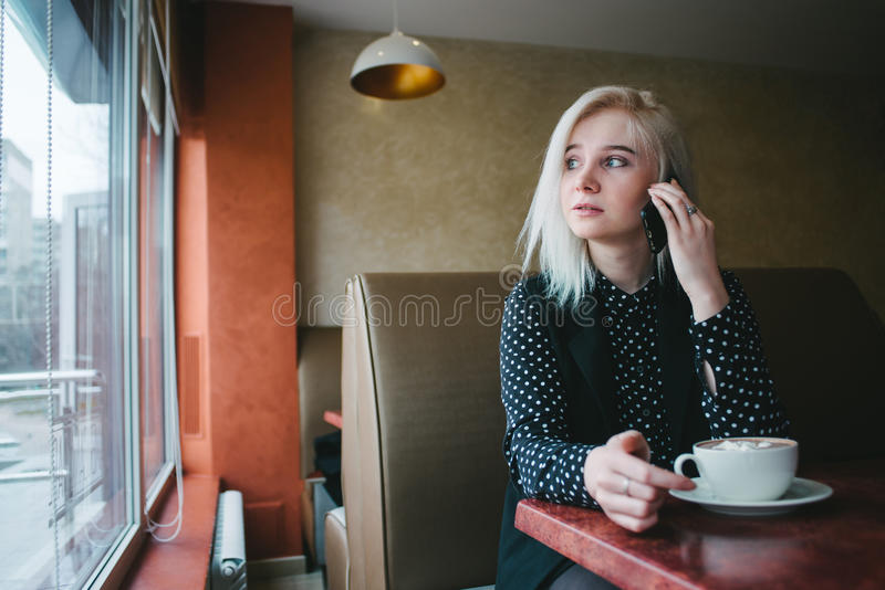 Portrait of a young girl student sitting in a cafe, drinking coffee and talking on the phone looking in the window stock images