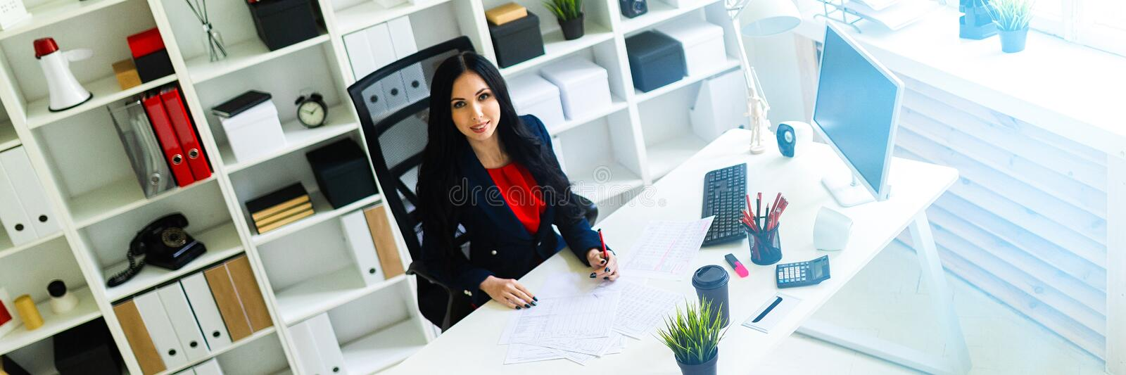 Beautiful young girl fills the documents, sitting in the office at the table. royalty free stock photography