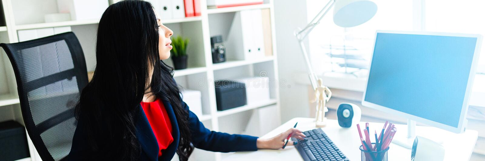 Beautiful young girl working with computer and documents in the office at the table. royalty free stock image