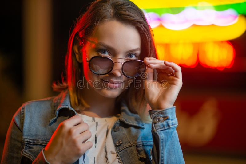 Portrait of a young girl in sunglasses, with creative light on a background of neon lamps stock image