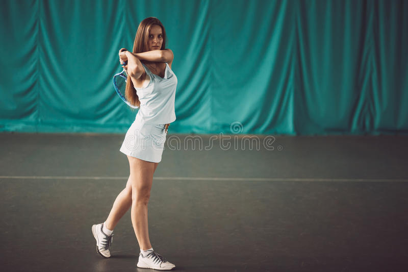 Portrait of young girl tennis player in a tennis court indoor royalty free stock photo