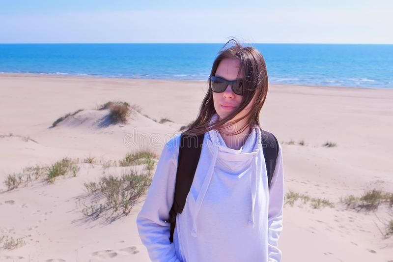 Portrait of young girl traveller with backpack on sea sand beach on vacation. Woman on empty eashore off-season. Portrait of young woman traveller with backpack stock images