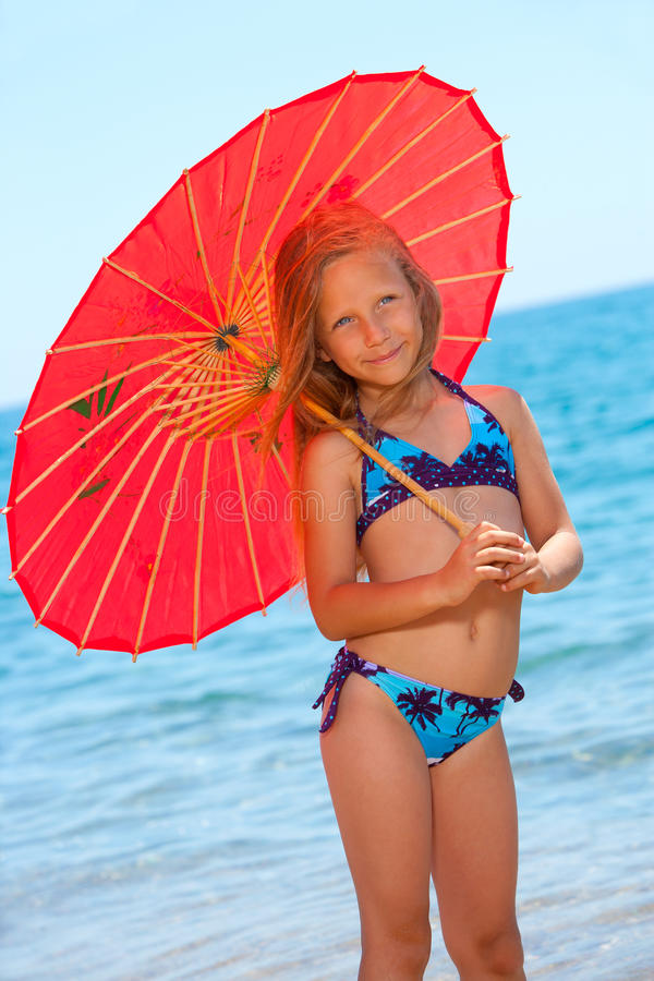 Portrait of young girl with umbrella on beach. stock photography