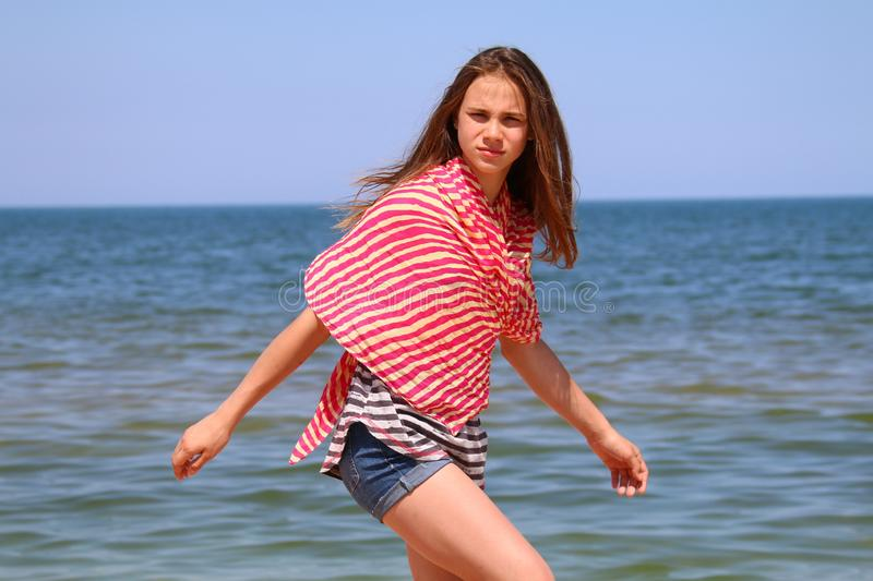 Portrait of a young girl walking in the summer on the beach royalty free stock images