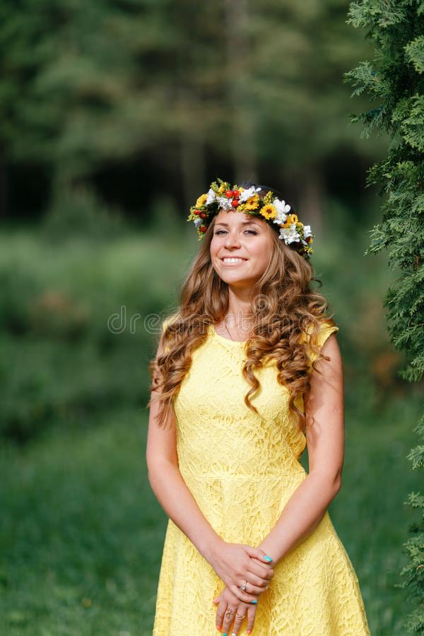 Portrait young girl in yellow dress with Flower wreath for head. Walking in park, Warm summer day. stock image