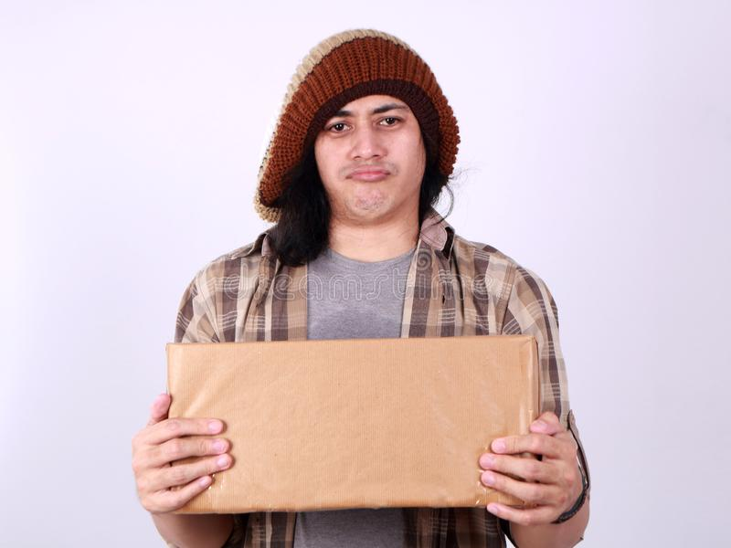 Courier Delivery Man Giving Box. Portrait of young good looking Asian courier delivery man giving box of parcel package, looking at camera amd smiling, isolated royalty free stock photo