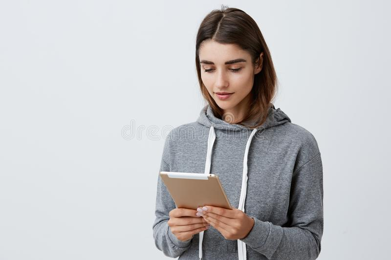 Portrait of young good-looking caucasian student girl with dark long hair in casual gray hoodie holding digital tablet royalty free stock image