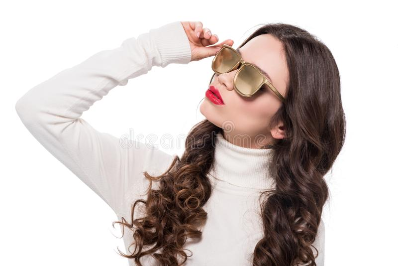 Portrait of young good-looking woman with bright makeup wearing gold opaque sunglasses, royalty free stock photography