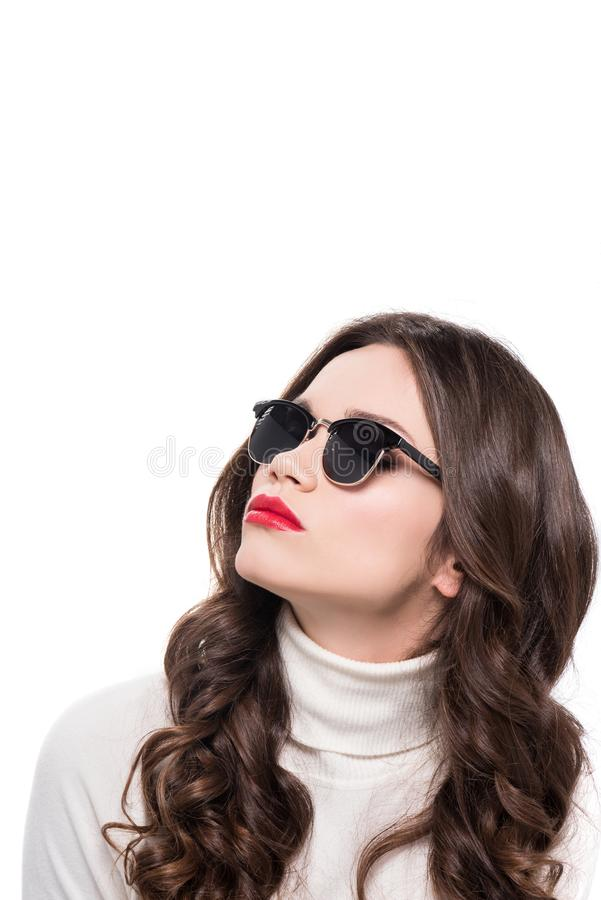 Portrait of young good-looking woman with bright makeup wearing trendy sunglasses and looking up, stock photography