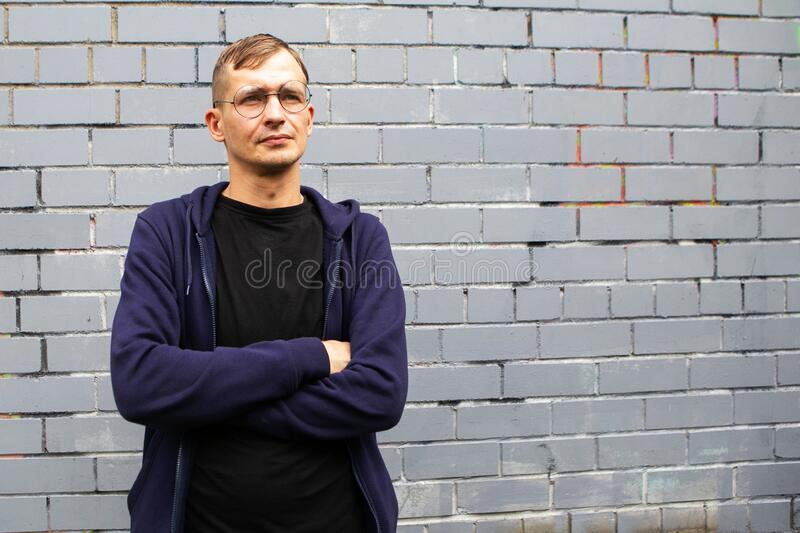 Portrait of young goodlooking man against grey brickwall. Lots of copyspace royalty free stock image