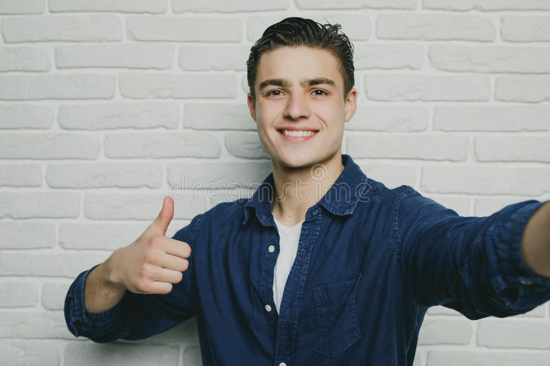Portrait of young goodlooking man with thumbs up against white brickwall. Portrait of young goodlooking man against white brickwall stock images