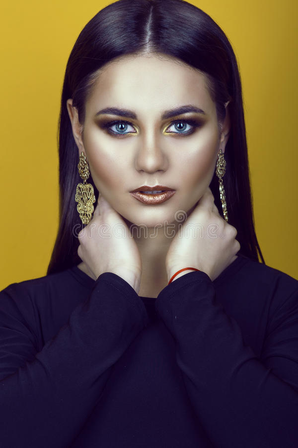 Portrait of young gorgeous blue-eyed dark-haired model with professional make up in golden colors wearing black top and earrings stock image