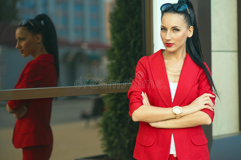 Portrait of young gorgeous dark-haired businesswoman in classic red suit and golden watch with sunglasses on her head stock photos