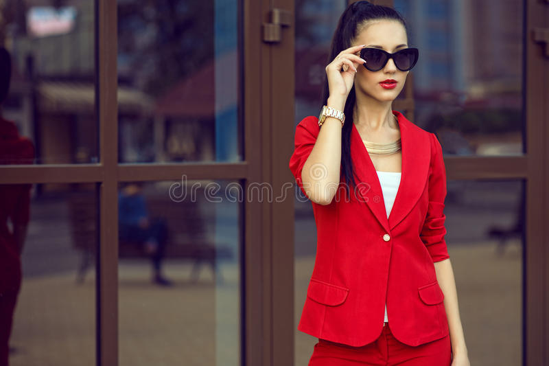 Portrait of young gorgeous dark-haired businesswoman in stylish sunglasses and bright red suit stock photo