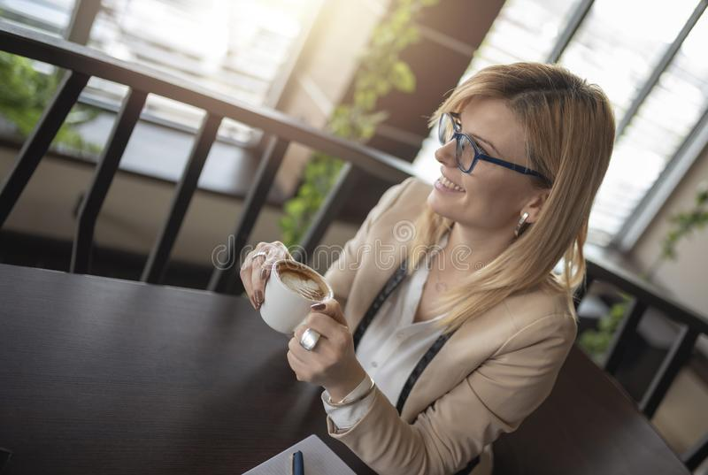 Portrait of young gorgeous female drinking cup of coffee and enjoying her leisure time alone stock photo