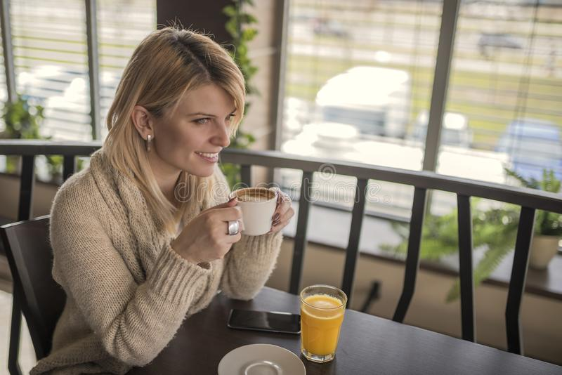 Portrait of young gorgeous female drinking cup of coffee and enjoying her leisure time alone royalty free stock image